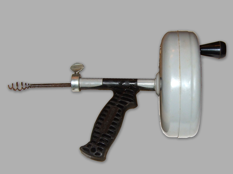 Handheld drain snake with white canister cable spool